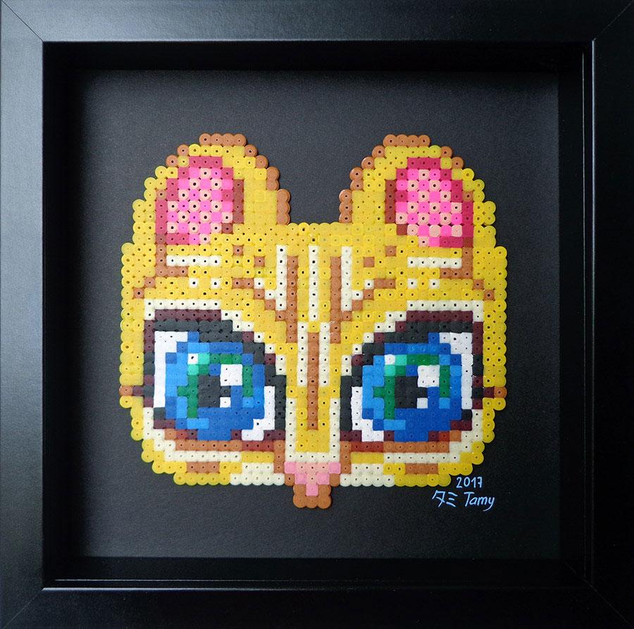 Petit tableau en perles à repasser sur papier noir représentant un masque de fauve dans les tons de jaune, et bleu, dans le style du pixel art