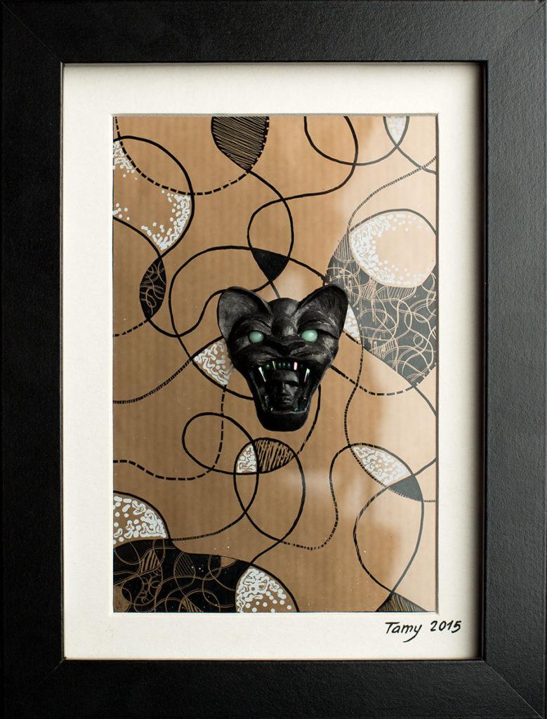 Modelage en pâte polymère et perles noir sur un fond en verre décoré et gravé, représentant une tête de fauve tenant entre ses crocs un visage.
