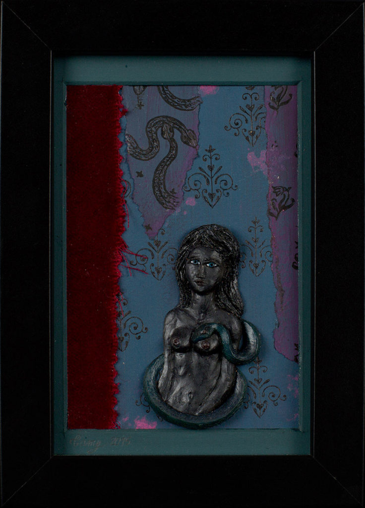 Modelage en polymère noir sur fond de tissu et carton, représentant un buste de femme nue entourée d'un serpent