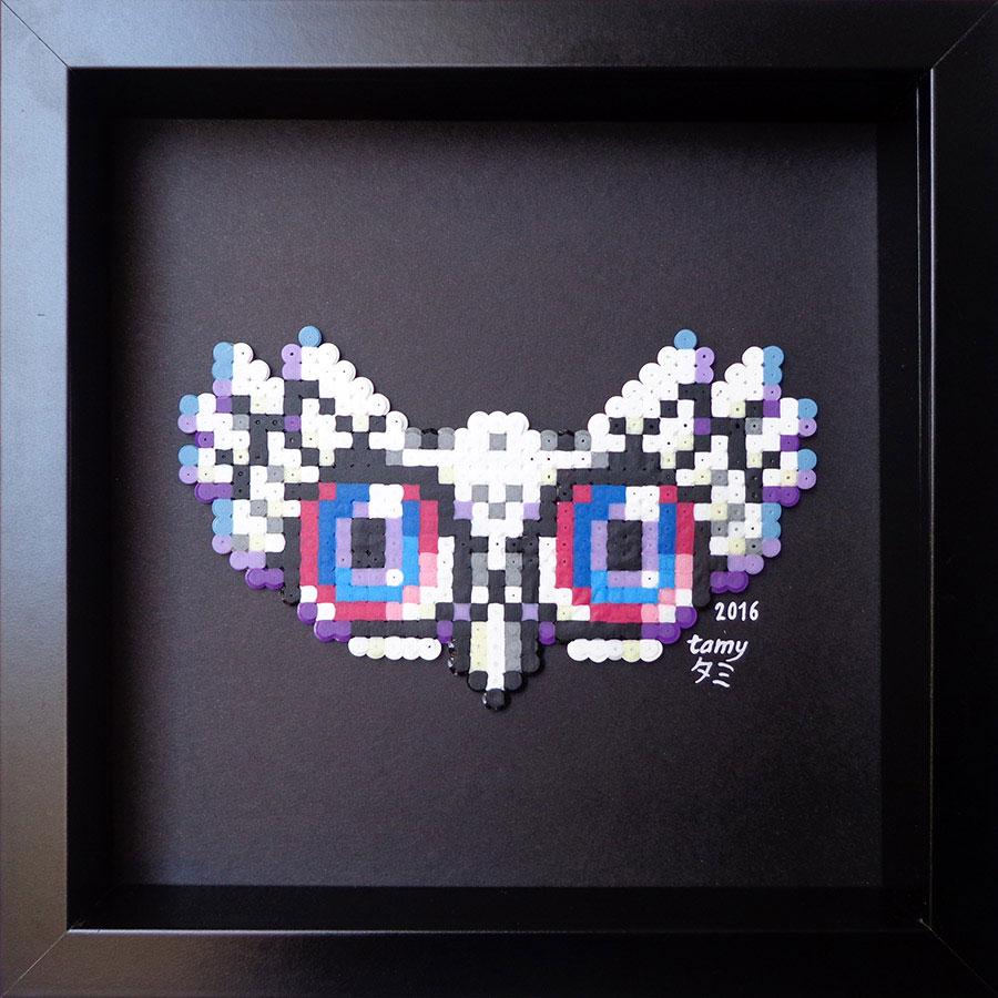 Petit tableau en perles à repasser sur papier noir représentant un masque de hibou dans les tons de blanc,et gris, dans le style du pixel art
