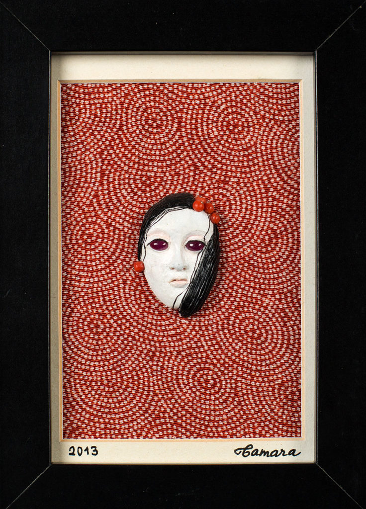 Modelage en polymère, perles de corail et cabochons sur fond de tissu japonais, représentant un masque de femme inspiré des masques japonais de theatre No