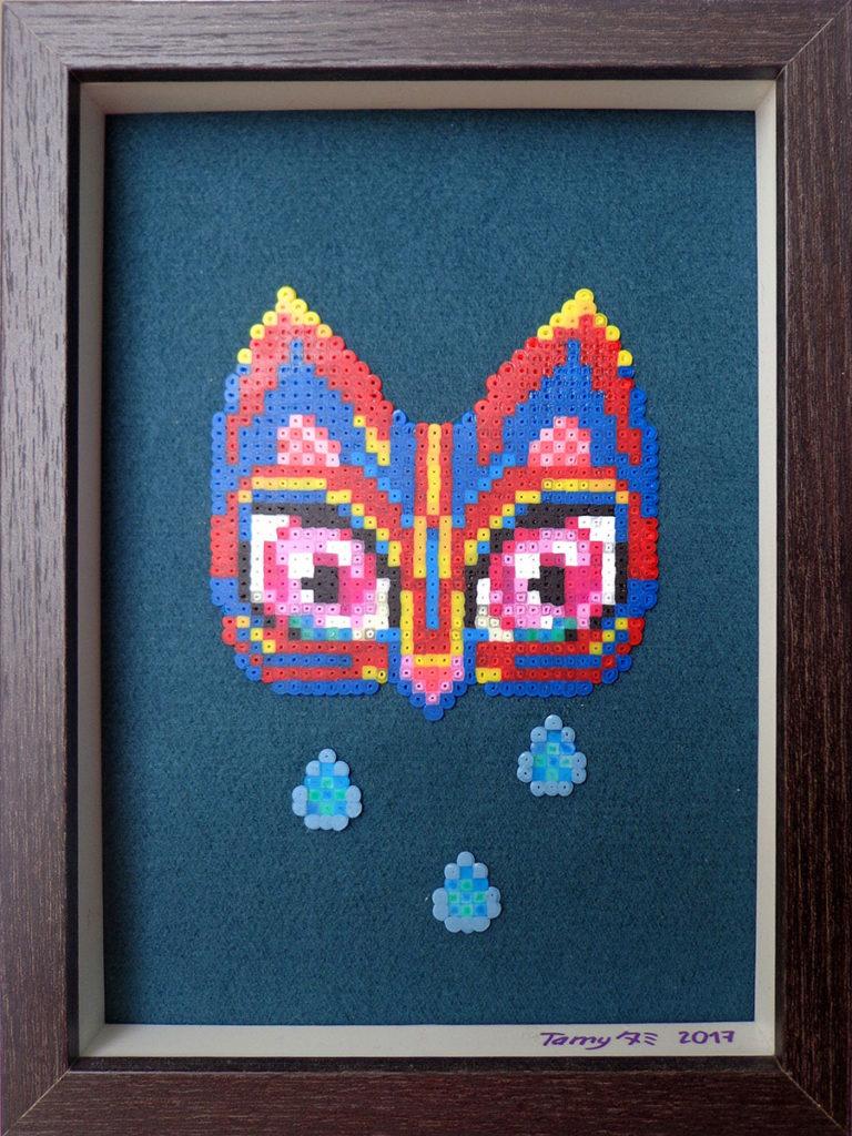 Petit tableau en perles à repasser sur tissu représentant un masque de fauve et des larmes dans les tons de rouge, bleu et jaune,avec le style du pixel art